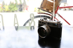 Color film camera on the black metal table - Top view with copy space. Color film camera with purple dry flower. The color film vintage camera is long lasting Royalty Free Stock Photo