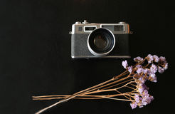 Color film camera with a notebook on the black metal table - Top. Color film camera with purple dry flower. The color film vintage camera is long lasting and Royalty Free Stock Image