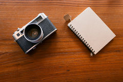 Color film camera and a notebook on the wooden table - Top view. Color film camera with a notebook. The color film vintage camera is long lasting and still Royalty Free Stock Photo