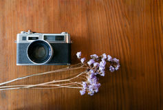 Color film camera with with purple dry flowers on the wooden table - Top view with copy space. Stock Image
