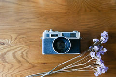 Color film camera with purple dry flowers on the wooden table - Top view with copy space. Stock Photos