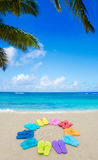 Color flip flops and drawing sun on sandy beach Royalty Free Stock Photo