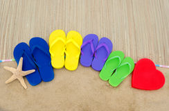Color flip flops and heart on sandy beach Royalty Free Stock Photography