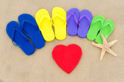 Color flip flops and heart on sandy beach Stock Images