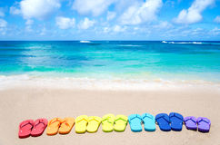 Color flip flops by the ocean. Color flip flops on sandy beach by the ocean in sunny day Stock Photos