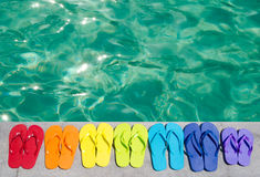 Color flip flops by the pool Stock Images