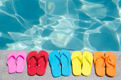 Color flip flops by the pool. Color flip flops by the swimming pool in sunny day stock photography