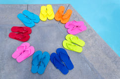 Color flip flops by the pool Royalty Free Stock Photo