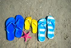 Color Flip flops on the sand. At the beach in summer royalty free stock image