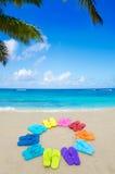 Color flip flops on sandy beach Royalty Free Stock Image