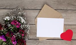 Color flowers, heart shape and envelope on wooden background. Valentine`s Day stock image