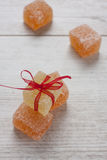 Color fruit jelly candies on the table. Close up of orange and yellow fruit jelly candies on the white wooden table royalty free stock images