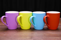 Coffee mugs. 4 color full coffee mugs on a natural wood table top with black background royalty free stock image