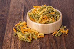 Color fusilli pasta,. Colorful bowl of uncooked fusilli pasta, on a rustic wooden background with copy space royalty free stock photos
