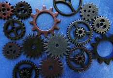 Color gears on blue. Assorted metal gears on blue textured background Stock Photo