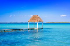 Color graded picture of a pier with clouds and blue water at the Laguna Bacalar, Chetumal, Quintana Roo, Mexico.  royalty free stock photography