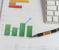 Color graphics on finance and business with a pen and computer keyboard. Royalty Free Stock Photo