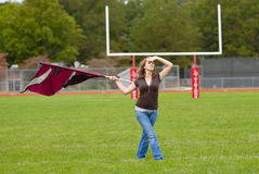 Color Guard Practice. Young woman practicing her color guard routine on a football field royalty free stock image