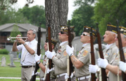 Color Guard Veterans in uniform with taps bugler. Color Guard veterans in uniform with guns lined up at cemetery for Memorial Day service with a man playing TAPS Royalty Free Stock Photos