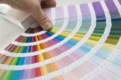 Color guide. Hand with color formula guide showing a color palette stock images