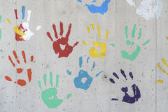 Color hand prints over a concrete wall. Red, yellow, green and blue paint. Good as a background image stock images