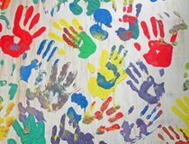 Color handprint diversity on concrete white wall. Many color handprints on concrete white wall. chaotic hands print heap diversity background, friendship concept royalty free stock images