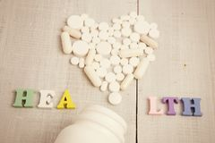 Color HEALTH  inscription and white heart of pills and capsules on white wooden desk Stock Photo
