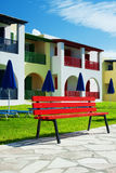 Color of holiday. Colored house in the sun country with red bench Royalty Free Stock Images