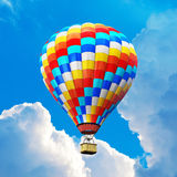 Color hot air balloon in the blue sky with clouds. Creative abstract colorful travel, tourism aerial transportation and freedom concept: 3D render illustration Stock Photos