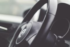Color image of a steering wheel inside a car. Color image of a hand holding a steering wheel inside a car Royalty Free Stock Photo
