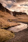 Seljalandsfoss waterfall and river in Iceland. Color image of Seljalandsfoss waterfall with river, clouds and path in Iceland in the Spring Royalty Free Stock Photo