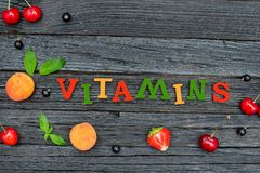 Color inscription Vitamins and fruits. Black wooden background. Food concept Stock Photos