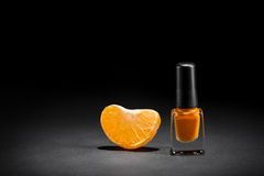 Color inspired by nature. Very bright colors inspired by nature. Mandarin segment near the tube of orange nail polish on black background. Cool picture for Stock Image
