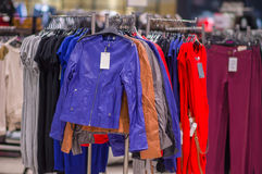 Color jackets, trousers on stands in mall Royalty Free Stock Image