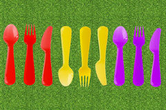 Color knives, spoons and forks on green grass, picnic concept Royalty Free Stock Photo