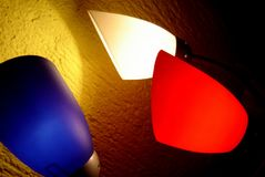 Color lamps over a yellow wall. Three different coloured coned lamps white, blue and red over a yellow wall royalty free stock images