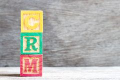 Color letter block in word CRM Customer Relationship Management on wood background stock image