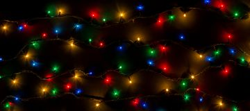 Color lights of a garland on black background Royalty Free Stock Images