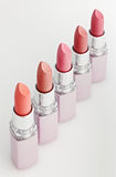 Color lipsticks arranged in line isolated on white. Top view royalty free stock photo