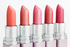 Color lipsticks arranged in line on white. Color lipsticks arranged in line isolated on white stock images