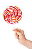 Color lollipop in child hand  on white Stock Photos