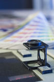 Color management with magnifying glass and color swatches Royalty Free Stock Photos