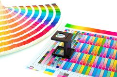Color management in printing process with magnifying glass and paint guide. royalty free stock photo