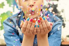 Color manicure. Fashionable girl with bright colorful nail designs blows confetti in her hands.Nails art.Color manicure royalty free stock images