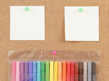 Color markers with notes on cork board Stock Image