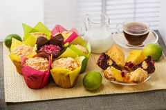 Color muffins in multi-colored paper, with milk, a cup of coffee and limes on mat from bamboo Royalty Free Stock Photo