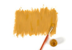 Color of mustard hand-painted daub with paint brush and gouache jar. Color of mustard gouache hand-painted daub with used paint brush and a gouache jar Stock Photography
