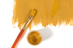 Color of mustard hand-painted daub with paint brush and gouache jar. Color of mustard gouache hand-painted daub with used paint brush and a gouache jar Royalty Free Stock Photo