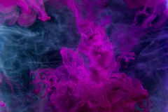 Color paint drops in water. Ink swirling underwater. Cloud of silky ink collision on black background. Colorful abstract smoke explosion animation. Close up Stock Images