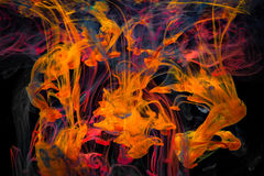 Color paint drops in water. Ink swirling underwater. Cloud of silky ink collision on black background. Colorful abstract smoke explosion animation. Close up Stock Photos